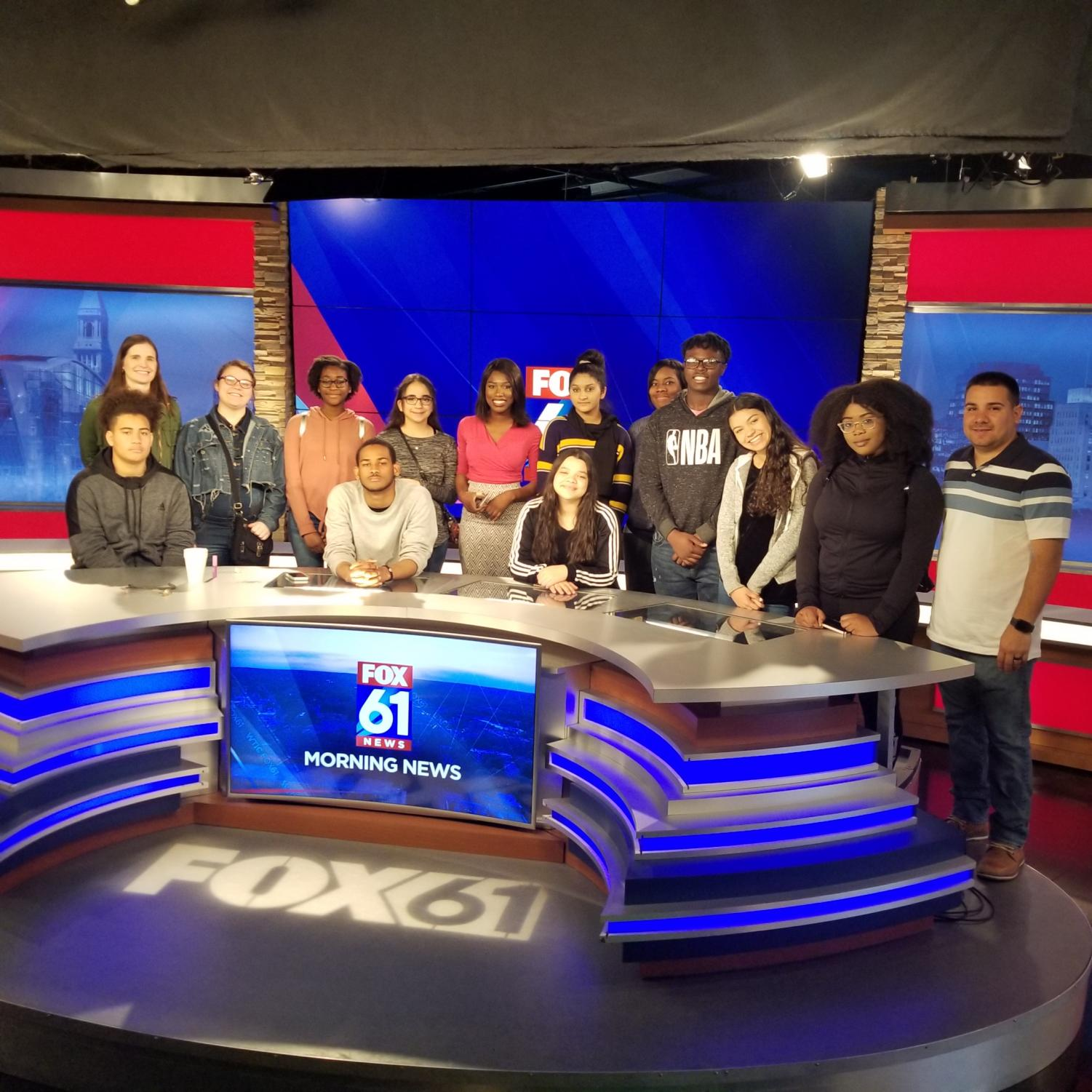 The+WHHS+group+poses+with+Aisha+Mbowe+behind+her+anchor+desk.