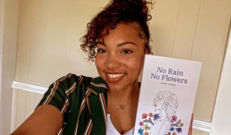 "Aianna Thomas, author of ""No Rain No Flowers"", poses next to a copy of her book."